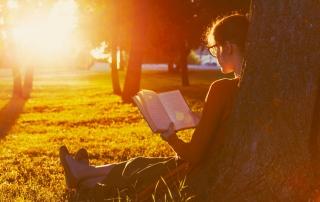 Vrouw zittend lezend tegen boom